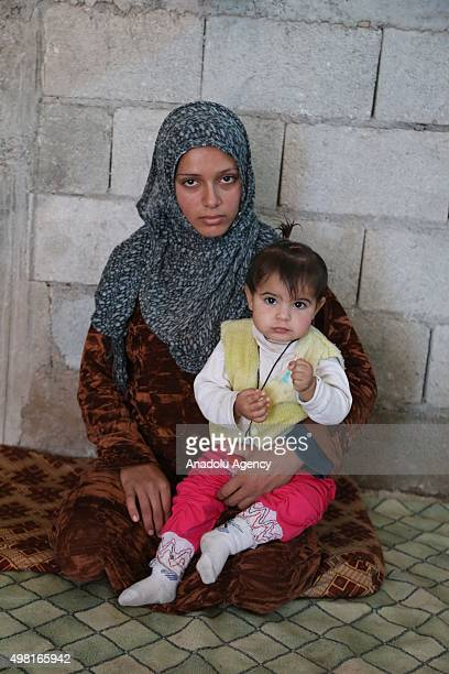 Syrian refugee woman fled from her home due to civil war is seen with her baby at a house in Reyhanli district of Hatay on November 21 2015 Syrian...