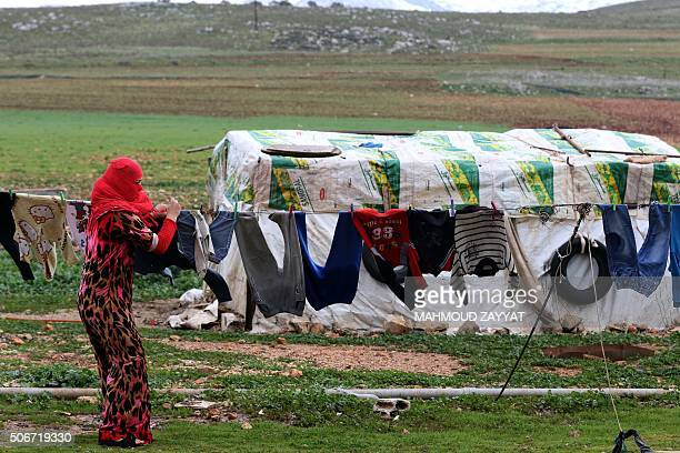 A Syrian refugee woman from Aleppo hangs her laundry at an unofficial refugee camp in the southern Lebanese village of Ibl alSaki on January 25 2015...