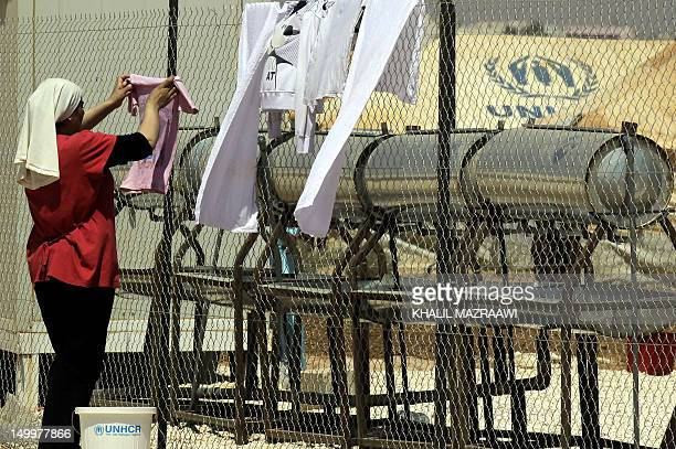Syrian refugee woman hangs her washing on a fence at the Zaatari refugee camp in the Jordanian city of Mafraq near the border with Syria on August 6...
