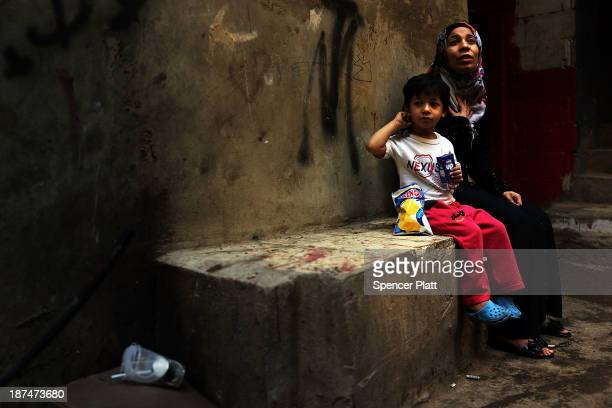 Syrian refugee woman pauses with her child in a neighborhood with a high concentration of Syrian refugees on November 9 2013 in Beirut Lebanon...