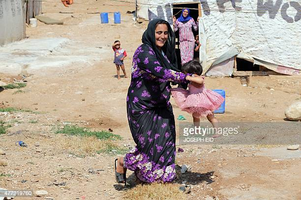 A Syrian refugee woman plays with a child at an unofficial refugee camp in the area of Arida north of Beirut on June 15 2015 Rights group Amnesty...