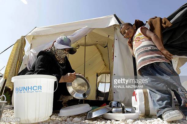 A Syrian refugee woman washes plates outside a tent at the Zaatri refugee camp near the Jordanian border with Syria on September 11 2012 The number...