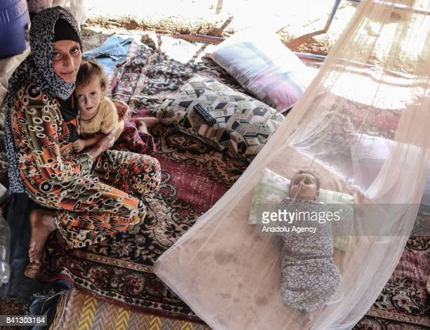 Syrian refugee woman with two babies fled from Syrian city of Aleppo due to Assad Regime and Daesh terrorists' assaults is seen inside a makeshift...
