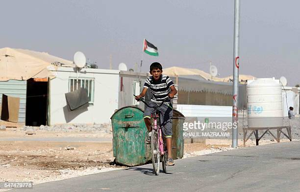 A Syrian refugee youth rides a bicycle at the Zaatari refugee camp located close to the northern Jordanian city of Mafraq near the border with Syria...
