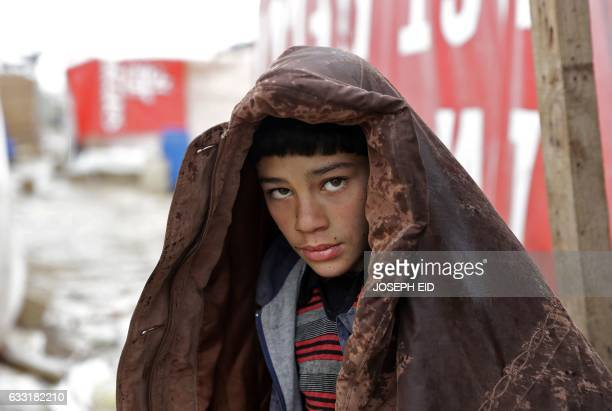 A Syrian refugee youth walks in an alley at an unofficial refugee camp refugee camp in the village of Deir Zannoun in Lebanon's Bekaa valley on...