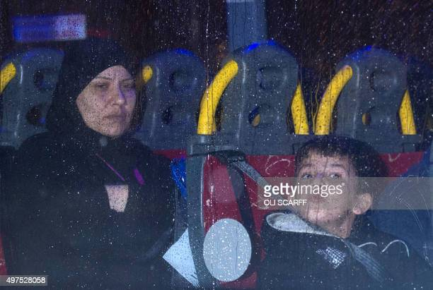 Syrian refugees are driven away after landing at Glasgow airport Scotland on November 17 2015 A first flight carrying Syrian refugees to Britain...
