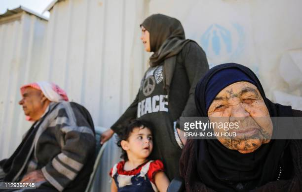 Syrian refugees are picture at a refugee camp in the village of Mhammara in the northern Lebanese Akkar region on March 9 2019