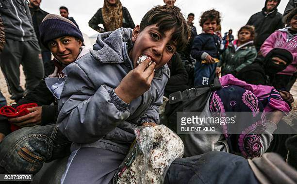 TOPSHOT Syrian refugees are pictured in a camp as Syrians fleeing the northern embattled city of Aleppo wait on February 6 2016 in Bab alSalama near...
