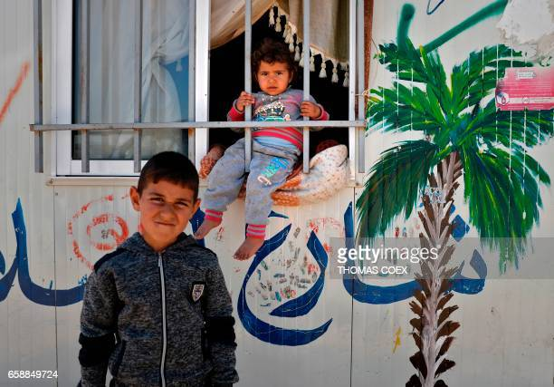 Syrian refugees are seen at the Zaatari camp which shelters some 80000 Syrian refugees on the Jordanian border with warravaged Syria on March 28 2017...
