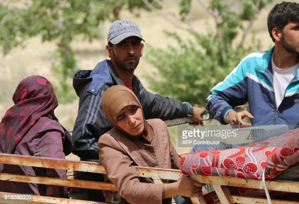 Syrian refugees are seen on the back of a pick up truck in the Lebanese eastern border town of Arsal as they head towards the Syrian region of...