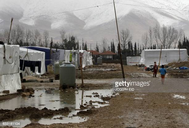 Syrian refugees are seen walking at an unofficial refugee camp near a snow covered mountain in the village of Deir Zannoun in Lebanon's Bekaa valley...