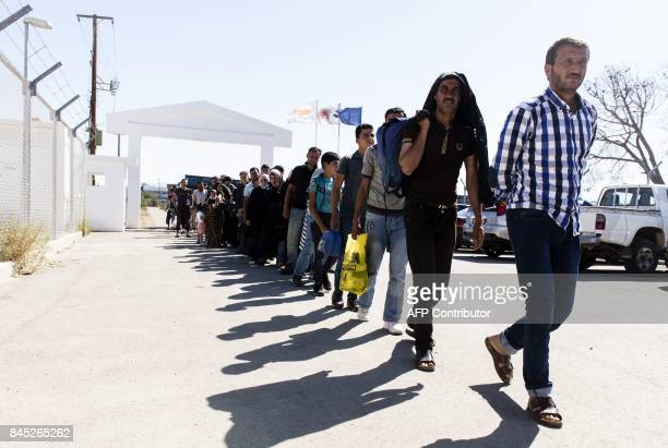 Syrian refugees arrive at the Kokkinotrimithia refugee camp some 20 kilometres outside the Cypriot capital Nicosia on September 10 after they were...