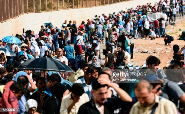 Syrian refugees arrive at the Oncupinar crossing gate close to the town of Kilis south central Turkey in order to cross to Syria for the Eid alAdha...