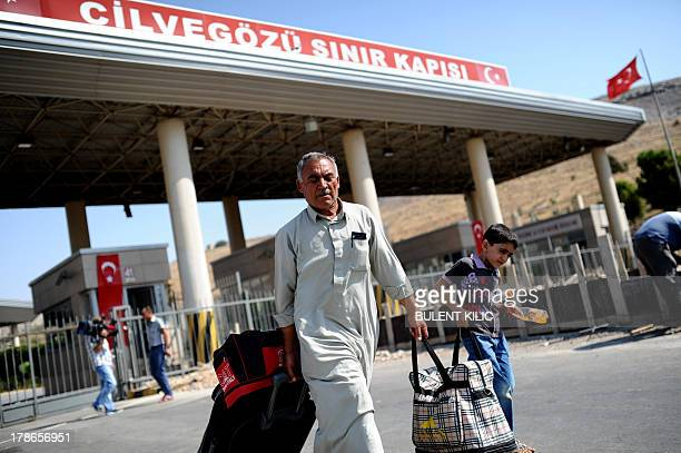 Syrian refugees arrive in Turkey from Cilvegozu crossing gate at Reyhanli in Antakya on August 30 2013 President Bashar alAssad vowed today to defend...