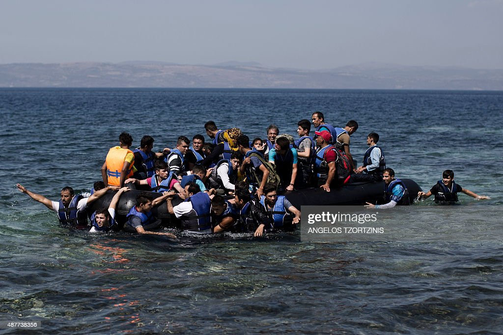 Syrian refugees arrive on the shores of the Greek island of Lesbos after crossing the Aegean Sea from Turkey on a inflatable dinghy on September 11, 2015. The EU unveiled plans to take 160,000 refugees from overstretched border states, as the United States said it would accept more Syrians to ease the pressure from the worst migration crisis since World War II. / AFP / ANGELOS