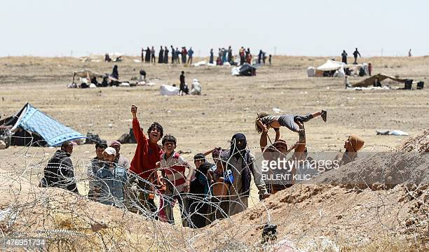 Syrian refugees ask for water in Akcakale at the Turkish border near the Syrian town of Tal Abyad on June 13 2015 Turkey said it was taking measures...