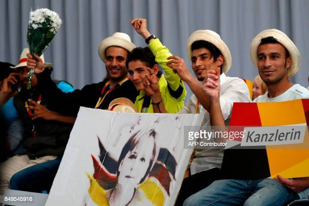 Syrian refugees attend an election rally of German Chancellor and Christian Democratic Union's main candidate Angela Merkel in Schwerin northern...