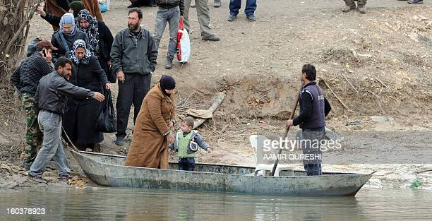 Syrian refugees board in a small paddle boat that will take them across the Orontes river to Turkey near the northern Syrian town of Darkush on...