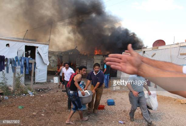 Syrian refugees carry away a machine as fire engulfs structures at an unofficial Syrian refugee camp in the Al-Marj area of Lebanon's eastern Bekaa...