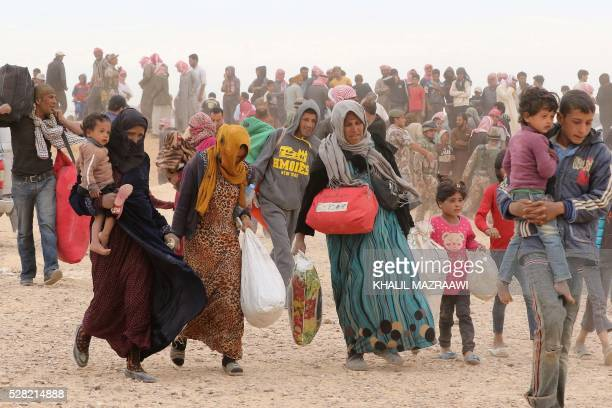 Syrian refugees carry their belongings as they wait to enter Jordanian side of the Hadalat border crossing a military zone east of the capital Amman...