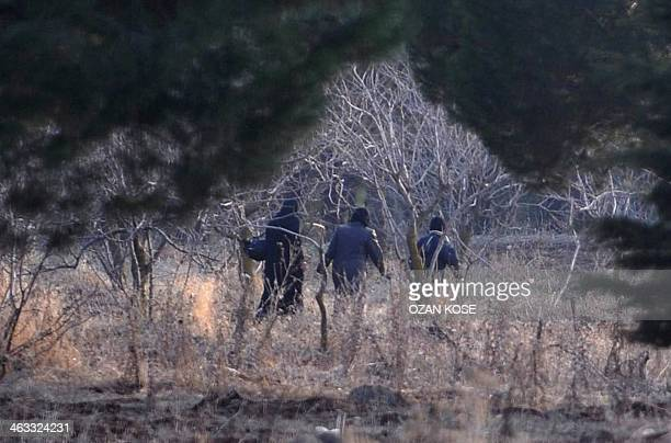 Syrian refugees cross the SyrianTurkish border illegally near the Oncupinar crossing gate on January 17 2014 in Kilis southern Turkey UN refugee...