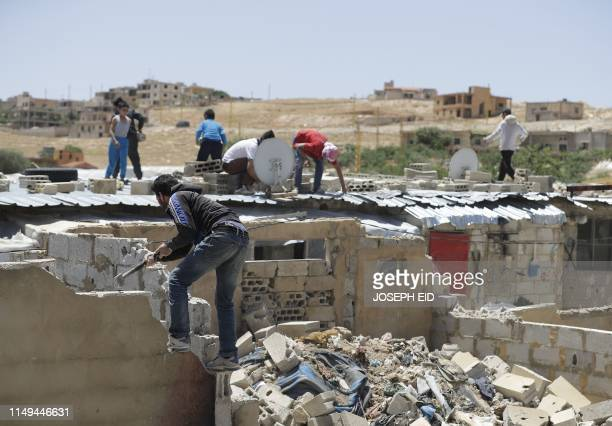 Syrian refugees demolish cement block shelters at a refugee camp in the northeastern town or Arsal in Lebanon's Bekaa valley on June 10 2019...
