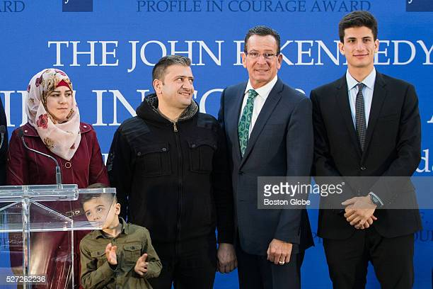 Syrian refugees Fatema Abdullah and their Ayham pose for a photograph with Connecticut Governor Dannel Malloy and Jack Schlossberg the grandson of US...