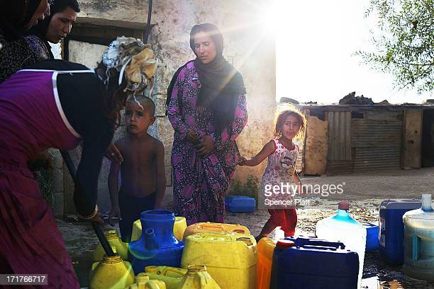 Syrian refugees fill jerry cans with water at a pump inside a camp for Syrians who have fled the fighting in their country on June 28 2013 in Baalbek...