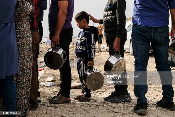 Syrian refugees fleeing the Turkish incursion in Northern Syria wait to receive water bread and lentil soup as more than 200 arrive at the Bardarash...