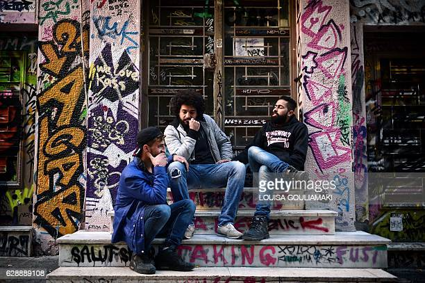 Syrian refugees from Aleppo Abu Habib Majd Ahmad and Abu Rmosh sit at the alternative neighborhood of Exarchia in Athens on December 9 home to many...
