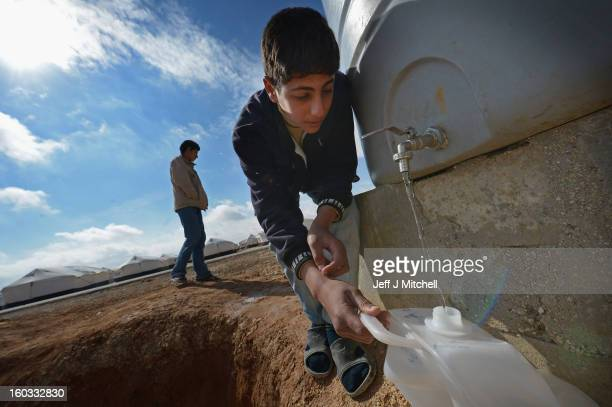 Syrian refugees gather water as they go about their daily business in the Za'atari refugee camp on January 29 2013 in Mafraq Jordan Record numbers of...
