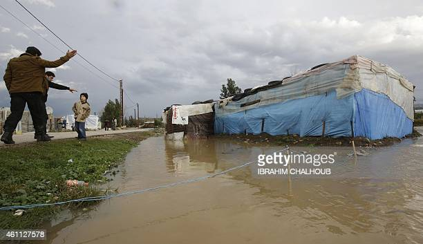 Syrian refugees gesture to a young boy standing near flood water from a winter storm that damaged the refugee camp in Akkara remote province of north...