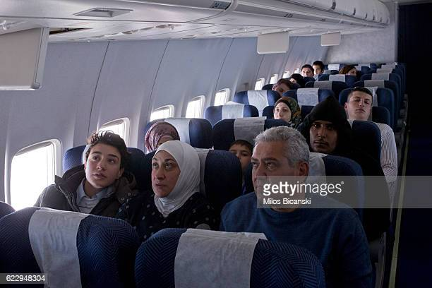 Syrian refugees Hassan Asaaid Alkhateb Mohamed and Lama watch a screen displaying their plane's route after boarding a special charter flight for...