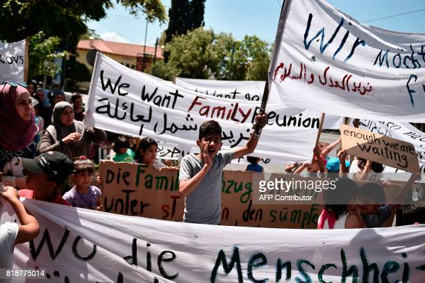Syrian refugees hold banners reading 'We want family reunion' outside the German embassy in Athens on July 19 2017 during a protest against delays in...