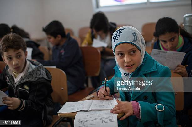 Syrian refugees live in a tented settlement in Turbide in the Bekaa Valley Lebanon March 14 2014 Syrian refugee children attend an afternoon school...