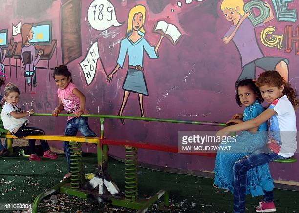 Syrian refugees living in Ouzaii coumpound play on a playground on July 17 2015 in the southern Lebanese city of Sidon during the celebration of Eid...