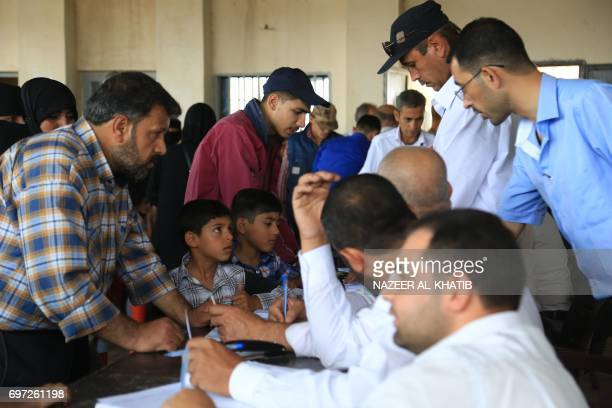 Syrian refugees living in Turkey register at the Bab alSalama crossing near the city of Azaz in northern Syria on June 18 after Turkish authorities...