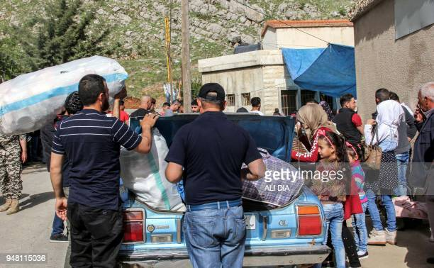 Syrian refugees load their luggage in the trunk of a car as they prepare to evacuate from the southern Lebanese village of Shebaa on April 18 to...