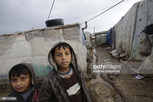 Syrian refugees look at the camera near temporary shelters at a refugee camp damaged by a winter storm in Akkara remote province of north Lebanon on...