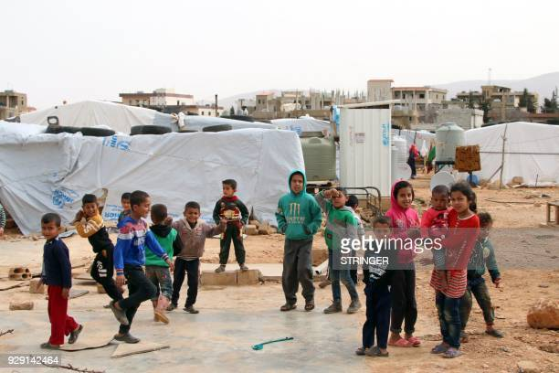 Syrian refugees play at an unofficial refugee camp in Lebanon's Bekaa valley on March 8 2018 / AFP PHOTO / STRINGER