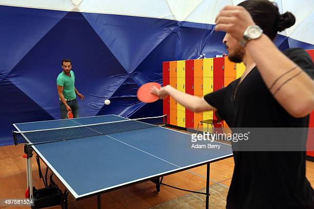 Syrian refugees play pingpong in an airdome used as a temporary shelter for refugees on September 26 2015 in Berlin Germany Following the attacks in...