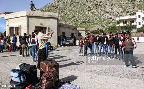 Syrian refugees pose for a group picture before their evacuation from the southern Lebanese village of Shebaa on April 18 to return home to their...