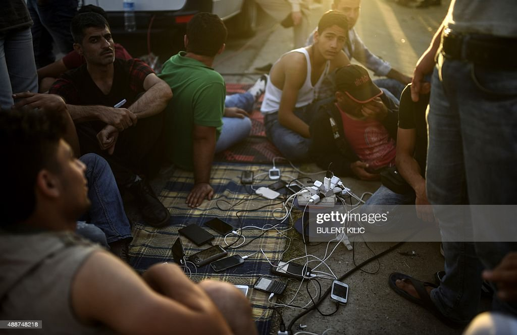 Syrian refugees re-charge their mobile phones from an extension attached to the van of a nearby TV crew as they rest beside the highway on their way to the border between Turkey and Greece in Edirne on September 17, 2015. Around 1,000 refugees remained stranded September 16 in the northwestern Turkish city of Edirne, near the Greek border, after being barred by Turkish authorities from continuing their journey to Europe.