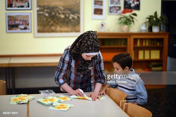 Syrian refugees Reem Haskour shows her son Ali AlAwis how to fold napkins while helping to prepare a breakfast for a pastors meeting at a church...