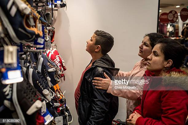 Syrian refugees Ronak and Zahra try to help their brother Ronnie choose some new shoes at an outlet store on Istiklal street on February 28 2016 in...