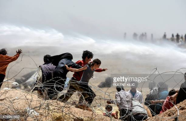Syrian refugees run away as Turkish soldiers use water cannon to move them away from fences at the Turkish border near the Syrian town of Tal Abyad...