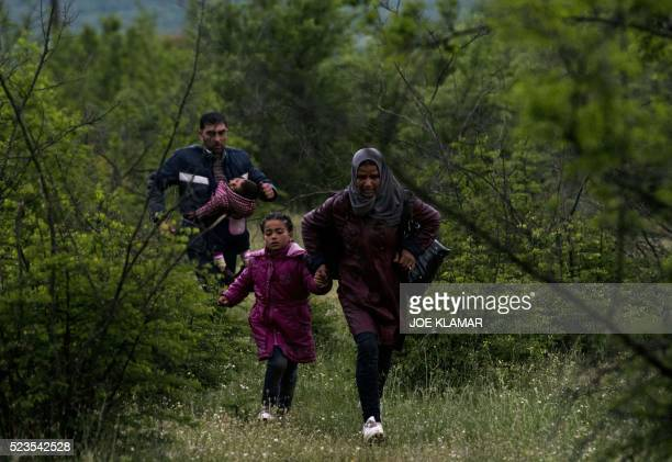 Syrian refugees run in a forest in Macedonia after illegally crossing GreekMacedonian border near the city of Gevgelija on April 23 2016 Some 50000...