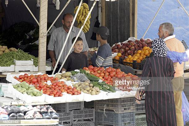 Syrian refugees shop for fruit and vegtables in a makeshift market in the Zaatari refugee camp a sevensquarekilometre camp that is home to more than...