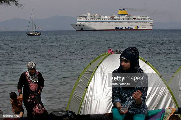 Syrian refugees sit on a beach by the of the port of Kos as the passenger ship 'Eleftherios Venizelos' backs into the quay on the Greek island of Kos...