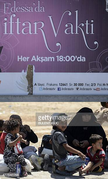 Syrian refugees sits under a sign referring to the Muslim fasting month of Ramadan which begins this week as they sit along a road that leads to the...